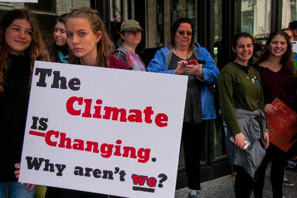 Image shows placard holding climate extinction protesters making the point that we all have to change and reduce carbon emissions.